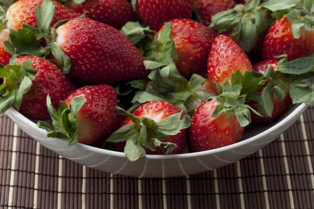 A cropped image of a white bowl with pink strawberries on a wooden table Stock Photo