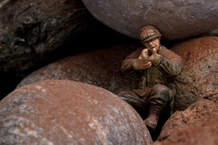 plastic soldier: Image of a military soldier with a rifle hiding on the rocks