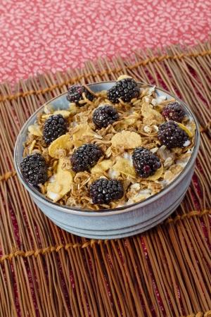caneberries: Bowl full of blackberry fruit and cornflakes on mat for breakfast