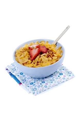 Bowl of cereals decorated with strawberry slices served with spoon and placed on top of a floral napkin Stock Photo - 17251219