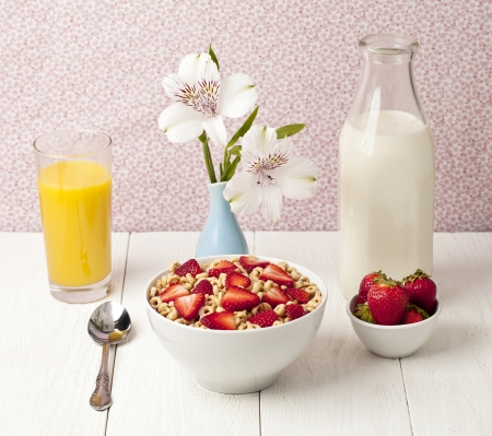 Bowl of ring cereals with strawberry slices, placed in a wooden table with a spoon, orange juice, milk, strawberries, and a base with flowers Stock Photo - 17251435