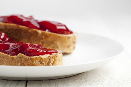 cropped image: Cropped image of a wheat bread with strawberry jam filling on a white plate Stock Photo