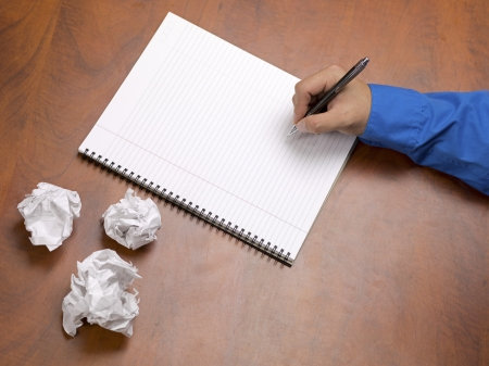 Close-up image of a person's hand writing on spiral writing pad on wooden desk with crumpled papers. Stock Photo - 17252969