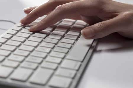 Cropped close-up image of a human hand on computer keyboard. photo