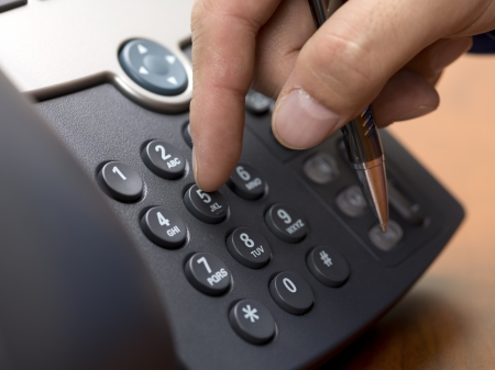 Close-up cropped shot of human hand dialing from a modern landline phone.