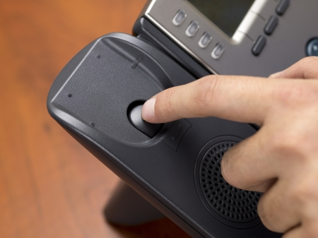 disconnecting: Close-up shot of a person disconnecting black landline phone.
