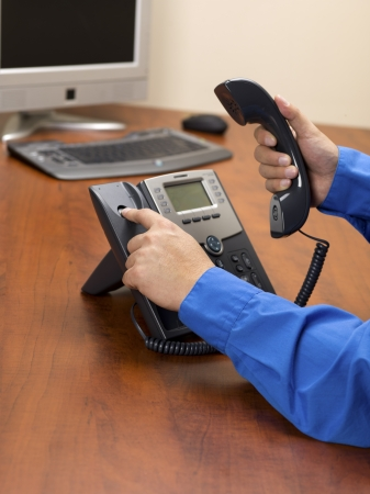 disconnecting: Close-up shot of human hand disconnecting black landline phone on office wooden desk. Stock Photo