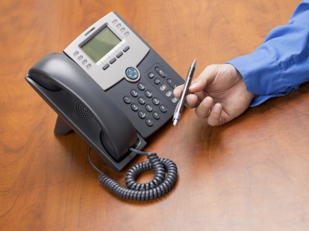 phone button: Close-up shot of human hand holding pen with landline phone on office wooden desk. Stock Photo