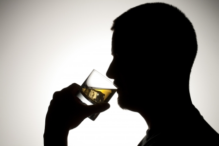 unhealthy living: Silhouette of a male drinking whiskey. Stock Photo