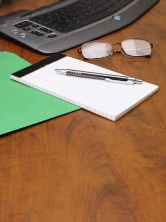Close-up image of notepad and pen with spectacles and keyboard on wooden desk. photo