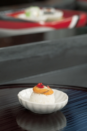 Close-up portrait of a Japanese cuisine on the white saucer with blurred maki on the background Stock Photo - 17252216
