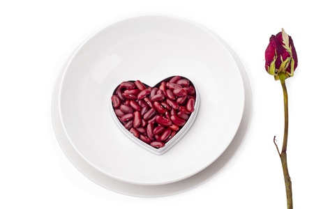 Kedney beans in heart shape container while rose isolated on white background. photo