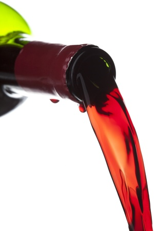 Close-up shot of Red wine being poured from the bottle on white background Фото со стока