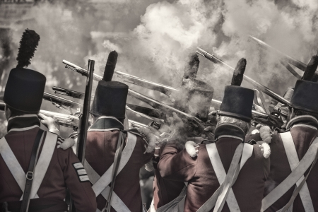 reenact: Back view of the soldiers firing the guns re-enacting the civil war in 1812