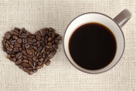 Close-up overhead shot of coffee cup with heart shape coffee beans. Stock Photo - 17252255