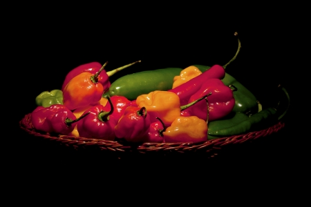 Close-up image a platter full of habanero peppers over the dark background