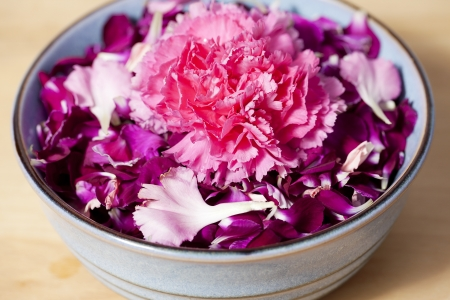 Horizontal image with purple carnation petals on a wooden table