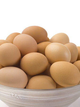 cropped image: Close-up cropped image of a clear bowl with brown eggs isolated on a white background