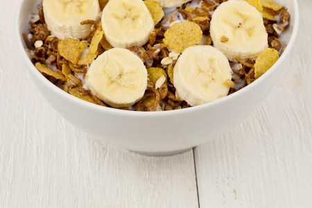A cropped image of a corn flakes bowl with slice banana on a wooden table Stock Photo - 17252455