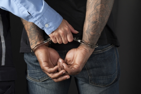 offence: Unrecognized male criminal with handcuffs arrested by a police officer Stock Photo