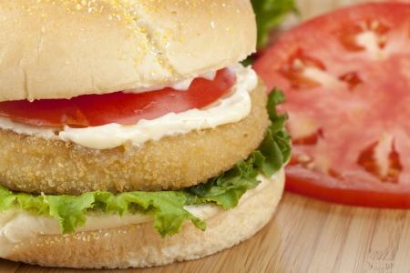 sandwich au poulet: Cropped image de sandwich au poulet croustillant sur une table en bois