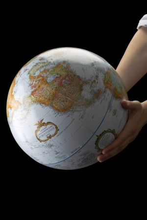 lifting globe: Image of earth globe in human hand against black background Stock Photo