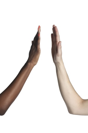 Two black and white female hands doing a high five over a white background