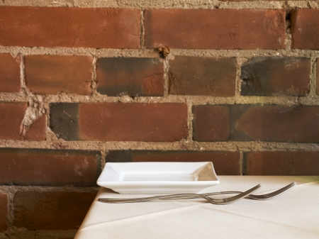 Close-up shot of fork and plate on restaurant table against bricked wall. photo