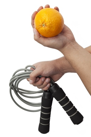 resistence: Close-up shot of human hands holding resistance band and orange fruit against white background. Stock Photo