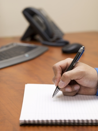 Close-up shot of a human hand writing on notepad with landline phone and computer keyboard in background. Stock Photo - 17252396