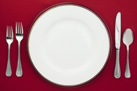 Plate and silverware on a red background