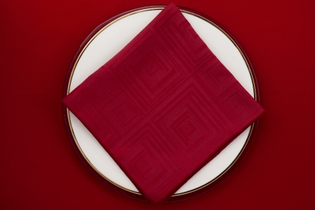 Image of plate with red napkin on red background photo