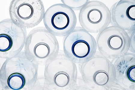 Close-up shot of stack of recyclable plastic bottles on white background. photo