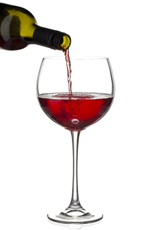 Close-up shot of red wine bottle pouring wine in wine glass against white background.