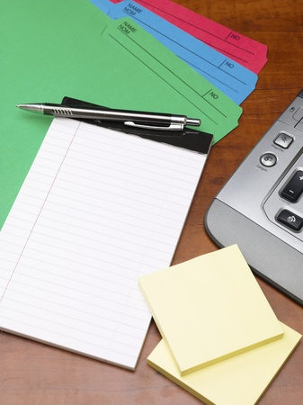 Close-up shot of a notepad and pen with adhesive note and keyboard on office desk. photo