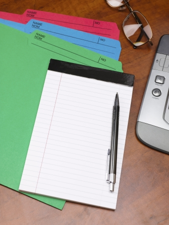 Close-up cropped shot of notepad with pen and colorful files on wooden desk. Stock Photo - 17252481