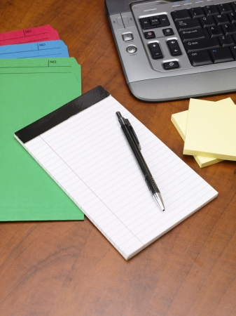 Close-up shot of a ballpoint pen with notepad and files on wooden office desk. Stock Photo - 17252446