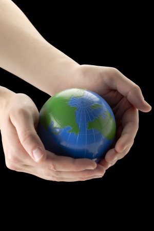 lifting globe: Close up image of globe in human hand against black background Stock Photo