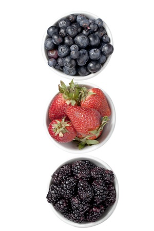Vertical image of a group of berries with strawberry, blueberry and blackberry over the white background
