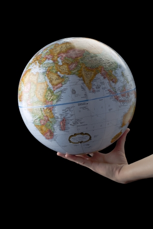 lifting globe: Image of human hand holding globe against black background