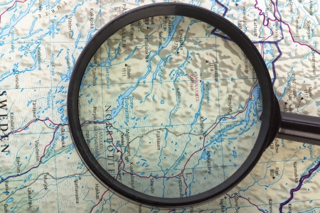 locating: Close-up image of magnifier searching on the world map