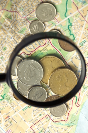 Image of magnifying glass over coins placed on map Imagens - 17258751