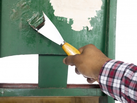 putty knives: Close-up of mans hand peeling a green paint on the old chair