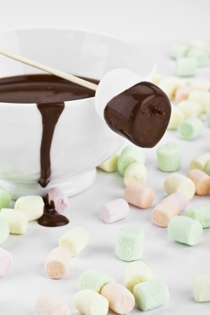 Close up image of marshmallow with melted chocolate and scattered marshmallow photo