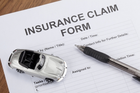 Car insurance concept image with toy car and pen placed on top of a blank insurance form