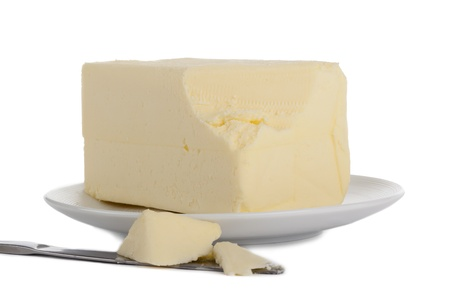 butterfat: Image of round plate with a bread knife slicing the butter on the white surface Stock Photo