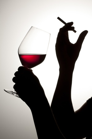 silhouette of woman drinking wine with cigarette