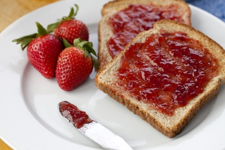 Close-up shot of bread slice with strawberry fruit and jam served on plate photo