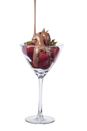Strawberries on a Martini glass that pouring melted chocolate against white background Imagens