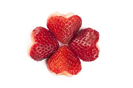 shaped: Close up image of four strawberries with a heart shaped and formed an image of flower against white background Stock Photo